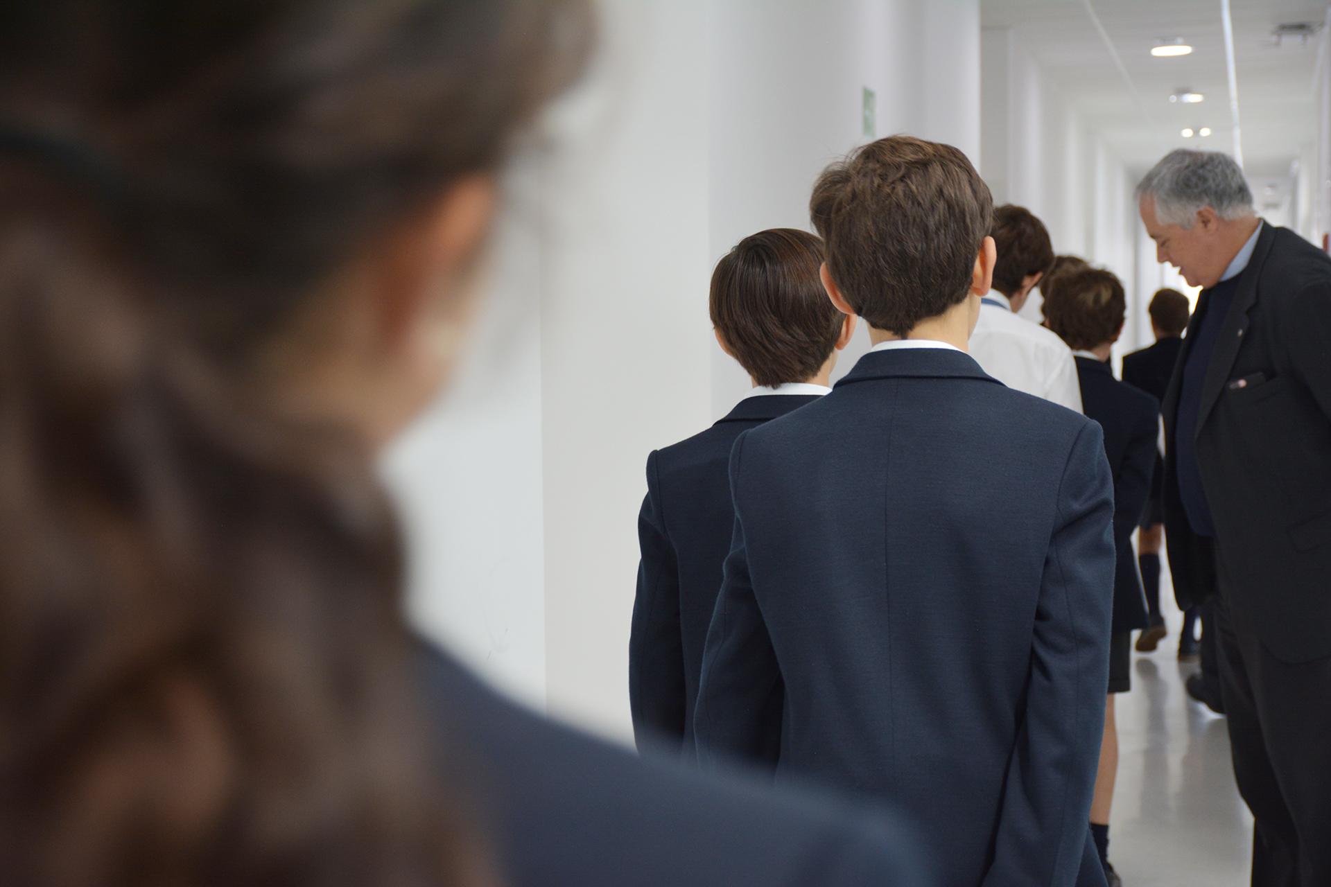 Alumnado junto a D. Manuel Orta Gotor en pasillo del Colegio CEU San Pablo Sevilla